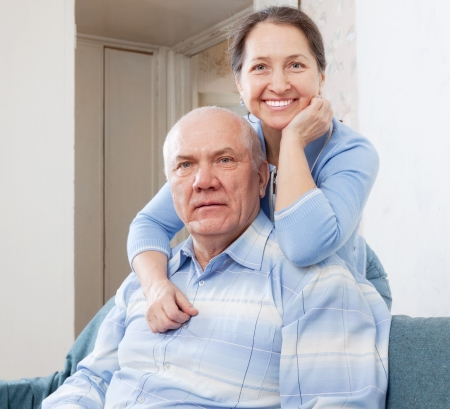 cheerful mature woman with senior husband in home interior photo