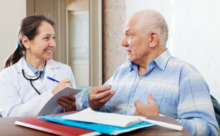 auscultoscope: friendly mature doctor talks with joyful senior man at hospital
