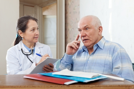 Woman doctor and senior patient near table with documents photo