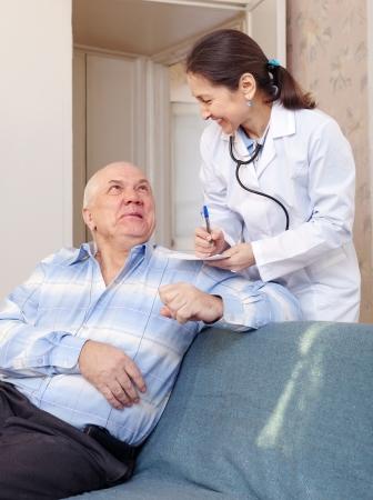 malaise: Happy senior man tells the mature doctor the symptoms of malaise