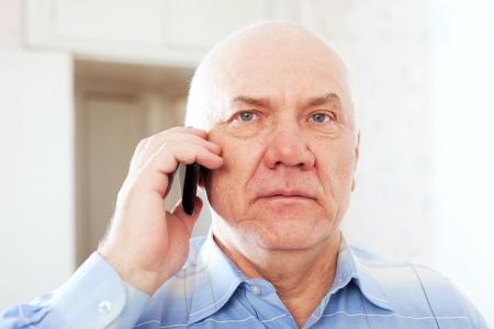 calm mature man speaks by phone photo