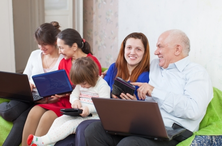 Happy family enjoys on sofa in livingroom with few laptops  photo