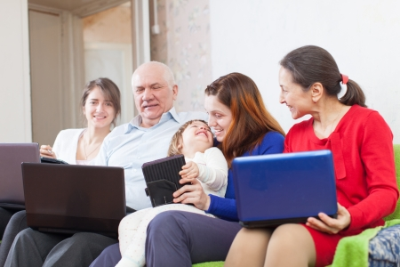 family sits on sofa in livingroom with laptops  photo