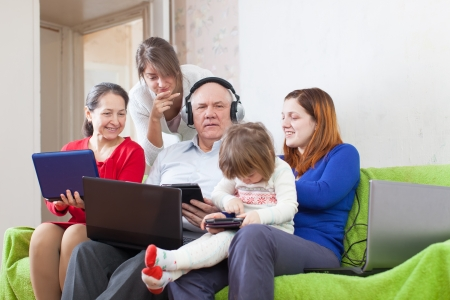 Happy family enjoys on sofa in livingroom room with few various laptops at home photo