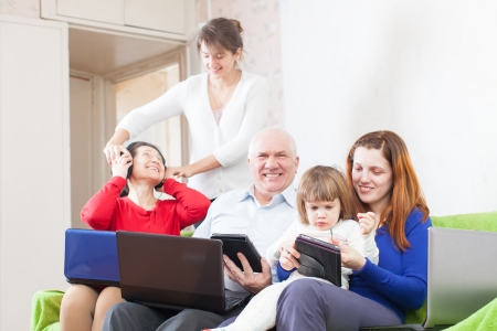 happy multigeneration family using few portable computers in home photo