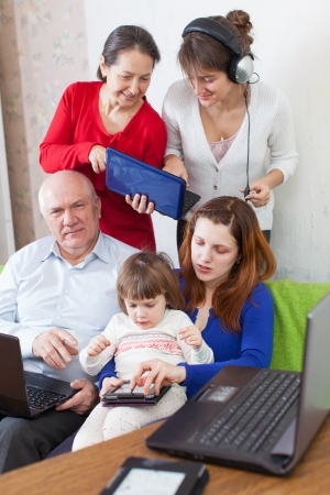 Happy multigeneration family uses few various electronic devices in home interior   photo