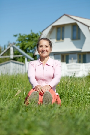 Happy mature woman sitting on lawn in front of new home photo