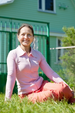 Happy woman sitting on lawn in front of new home photo