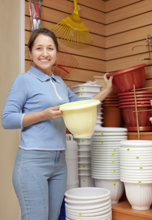 Smiling mature woman chooses plastic flowerpot at garden store Stock Photo - 21434294