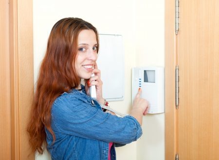 entry numbers: Young woman using house videophone