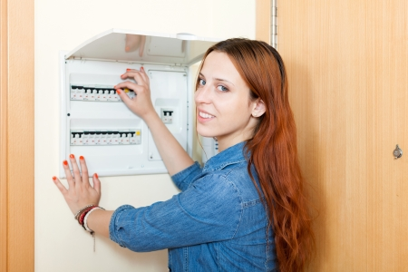 Young woman with light-switch in home in the hall Stock Photo - 21434398
