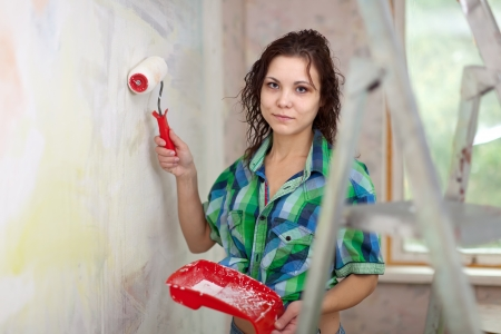 modifying: Happy girl paints wall with roller at home