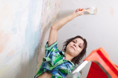 priming brush: Happy girl paints ceiling with brush at home  Stock Photo