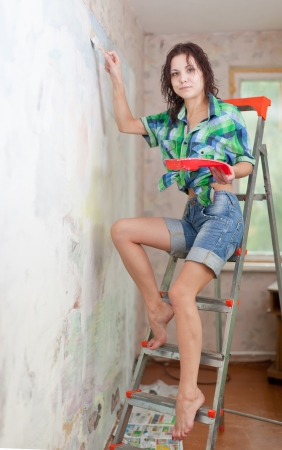priming brush: girl paints wall with brush at home Stock Photo