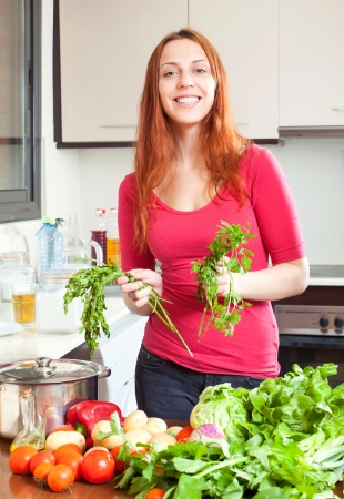 Portrait of happy  woman  with  fresh vegetables and greens in kitchen Stock Photo - 21434460
