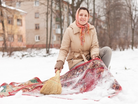 Russian woman cleans red rug with snow  photo