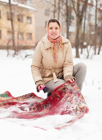 Russian woman cleans carpet with snow in winter  photo