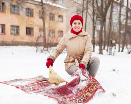 Smiling woman in red cap cleans carpet with snow in winter day    photo