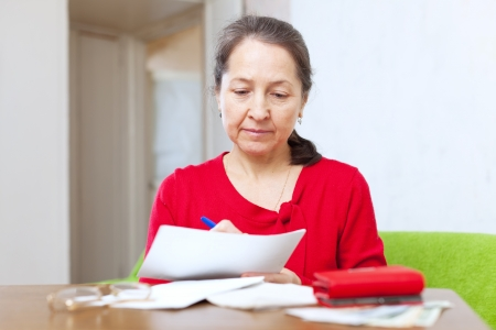 lamentable: serious mature woman fills in payment documents at home