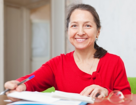 utility payments: gladful mature woman fills in documents at home