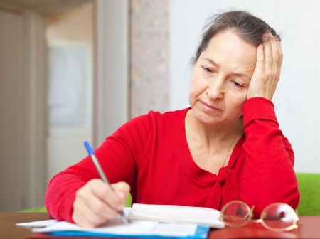 calculated: Sad mature woman with utility bills  at her home