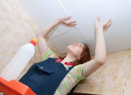 soffit cladding: Young woman glues ceiling tile at home