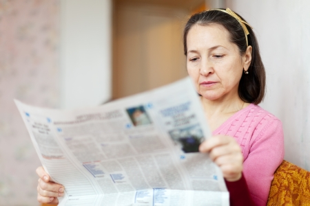 serious woman reading newspaper at home