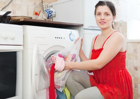 woman using bag for laundry in washing machine at her home photo