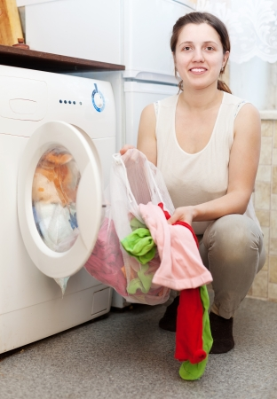 Young woman in white putting clothes with laundry bag in to washing machine and smiling photo