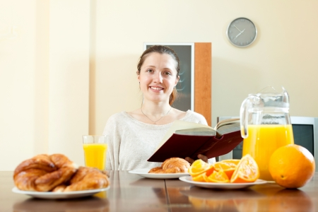 cheeful: Positive brunette woman having breakfast with juice in morning