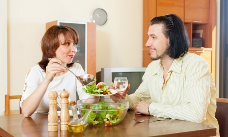 Man and woman eating salad vegetables in your home   photo