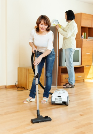 Happy woman and man doing housework together in home photo