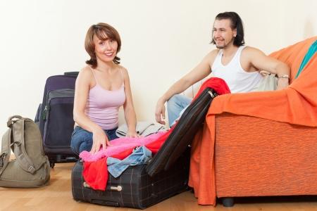 Couple with suitcases near door at home  photo