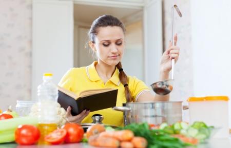 女性が台所で本で食品を調理 写真素材