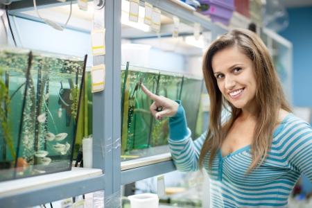 Woman chooses  fish in tank at petshop photo