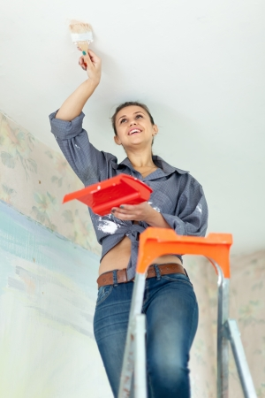 priming brush: Woman paints ceiling with brush at home