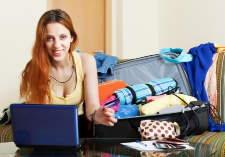 Female tourist buying tickets or reserving hotel online in the internet using laptop  photo