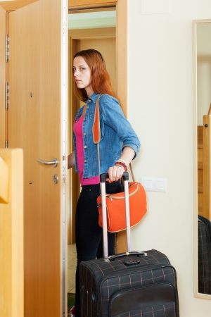 angry woman leaves home with suitcase because divorce photo