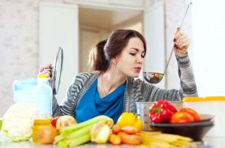 young woman tests food with ladle in the kitchen at home photo
