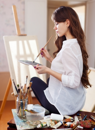 vrouwelijke kunstenaar met olieverf en borstels dichtbij schildersezel met leeg canvas