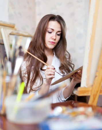 longhaired: Long-haired artist paints on canvas in workshop Stock Photo