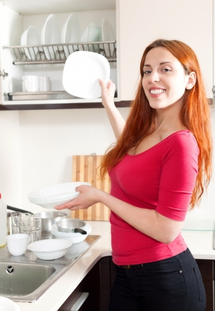 Positive housewife washing plates with in domestic kitchen photo