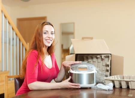 slow cooker: Young smiling woman with electric slow cooker in kitchen at home