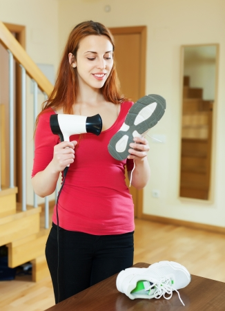 hairdryer:  woman in red warming shoes with hairdryer at home Stock Photo