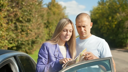 Traveler couple looking at the map on the country road Stock Photo - 21588559