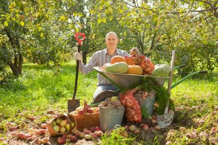 Happy man with vegetables harvest in garden photo