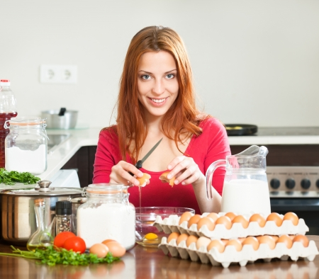 Smiling girl in red cooking omelet with eggs in home   photo