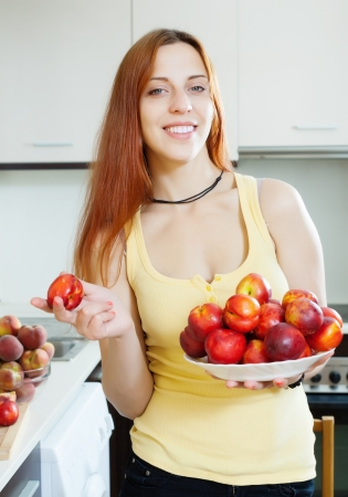 Smiling girl with nectarines at home kitchen photo