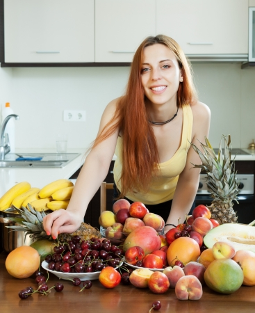 Positive long-haired woman with ripe fruits in home kitchen  photo