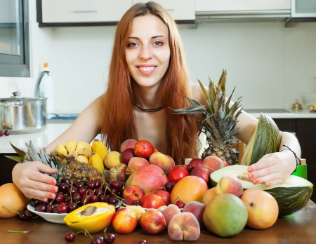 Happy long-haired girl with heap of fruits photo
